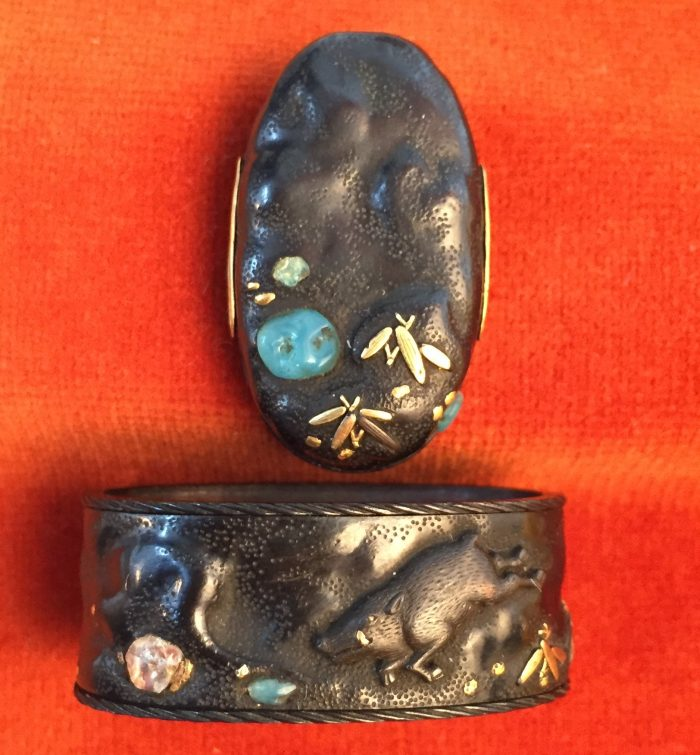 Fuchi-kashira with designs of boar, rocks and stream.