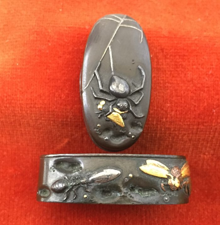 Fuchi-kashira with designs of spider holding a fly, and other insects.